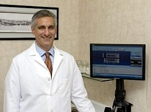 Drs. Rossetti stands in front of digital x-rays which is one of many dental services offered in Richmond, VA.